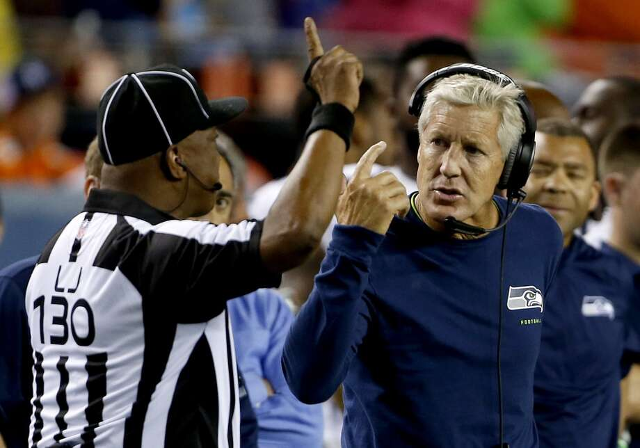 Seattle Seahawks coach Pete Carroll talks to line judge Darryll Lewis (130) during the second half of an NFL preseason football game against the Denver Broncos, Thursday, Aug. 7, 2014, in Denver. (AP Photo/Brennan Linsley) Photo: AP