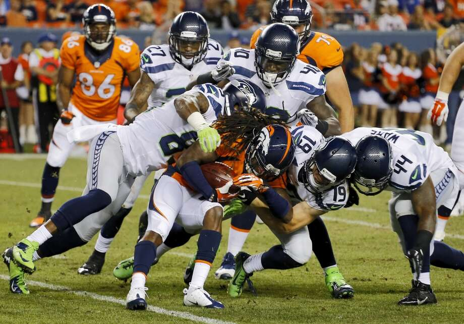 Denver Broncos  Isaiah Burse, center, is brought down by Seattle Seahawks   Ricardo Lockette, left, Bryan Walters (19), Spencer Ware (44), Tharold Simon (27) and Derrick Coleman (40) during the first half of an NFL preseason football game, Thursday, Aug. 7, 2014, in Denver. (AP Photo/Jack Dempsey) Photo: AP