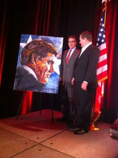 Texas Gov. Rick Perry receives the gift of a painting at the Red State Gathering 2014 in Fort Worth,
