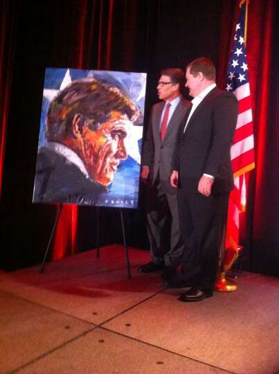 Texas Rick Perry receives the gift of a painting at the Red State Gathering 2014 in Fort Worth, Aug.