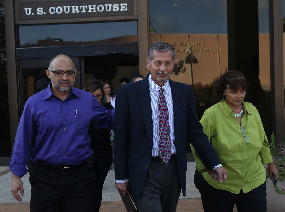 Anthony Mayhan (center), flanked by a family member (left) and his wife Rosemarie (right), leaves Federal Court Friday August 8, 2014 after being sentenced to probation for five years and 1,000 hours of community service on a bribery charge. Mayhan, a former San Antonio Independent School District employee and a former priest, pleaded guilty to a bribery charge for diverting contracts to himself. Photo: JOHN DAVENPORT, San Antonio Express-News / ©San Antonio Express-News/John Davenport