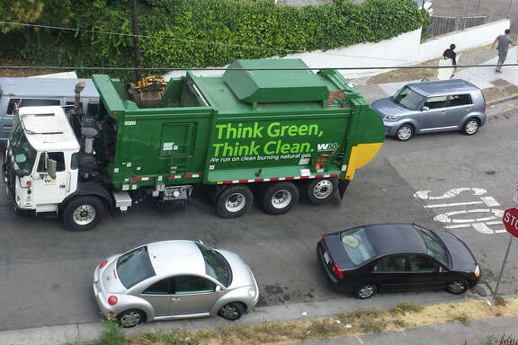 A Waste Management truck works a route in Oakland.