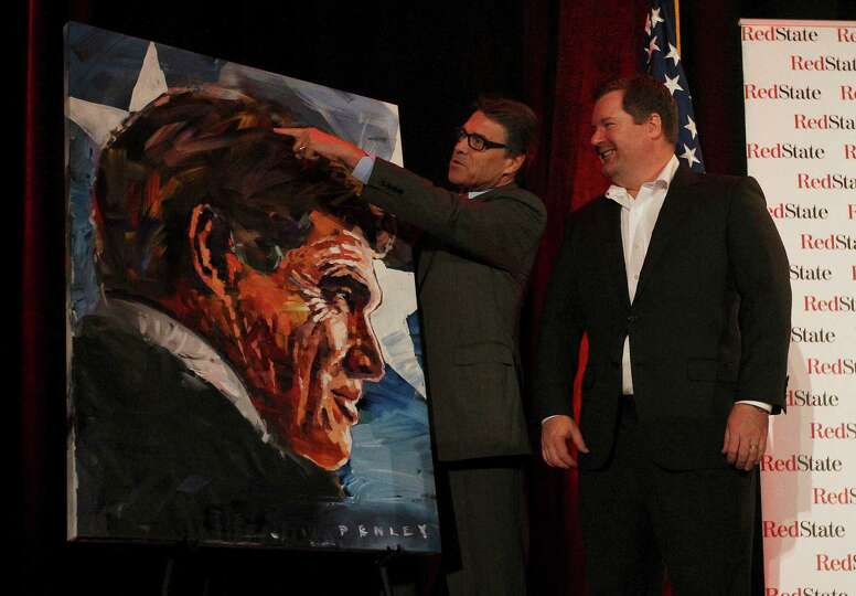 Governor Rick Perry (left) points to a part of Steve Penley painting given to him by RedState.com's