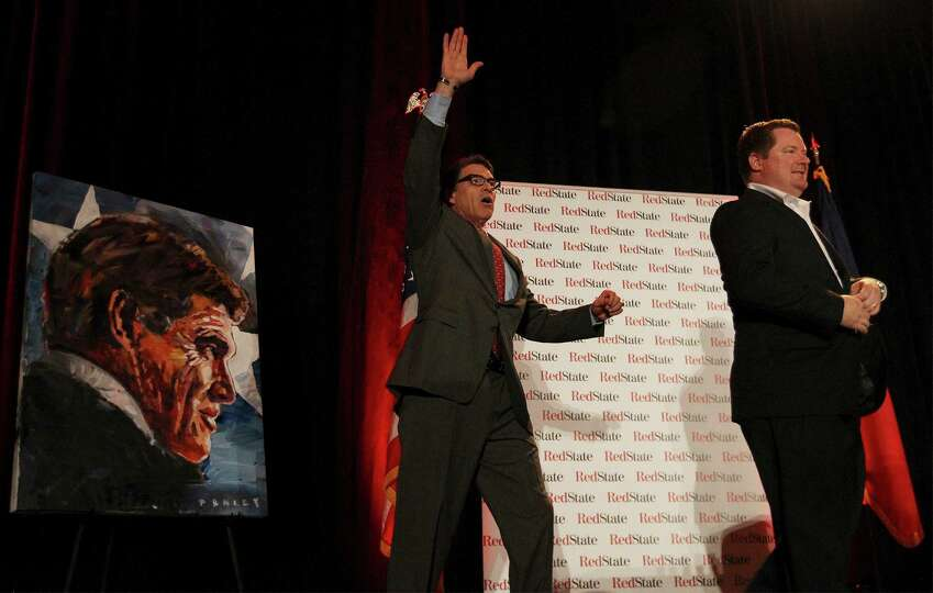 Governor Rick Perry (center) waves to the crowd after being presented with a painting by artist Stev