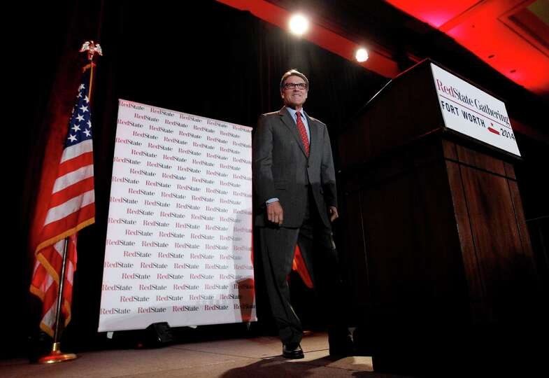 Texas Governor Rick Perry stands by the podium smiling as he acknowledges applause after delivering