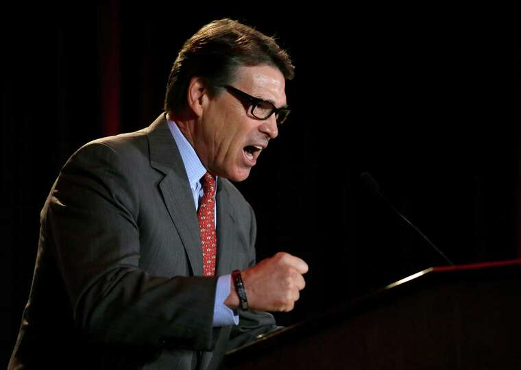 Governor Rick Perry balls up his hand in a fist as he addresses a group of nearly 300 in attendance