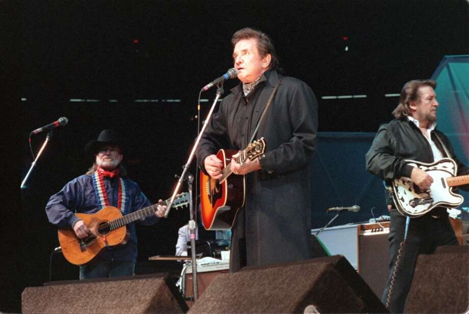 Johnny Cash (Center) and Willie Nelson (Left) and Waylon Jennings (Right) three of The Highwaymen performing at the Houston Rodeo, March 3, 1990. Photo: Paul Howell, © Houston Chronicle