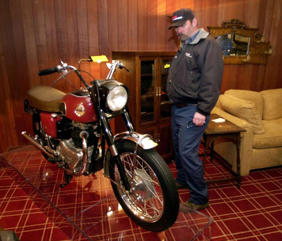 Peter Parker of Murfreesboro, Tenn., looks over a motorcycle that once belonged to Buddy Holly, at the home of country music star Waylon Jennings in Brentwood, Tenn., Thursday, Dec. 28, 2000. Jennings and his wife, singer Jesse Colter, moved to a smaller home in Chandler, Ariz. Photo: MARK HUMPHREY, AP