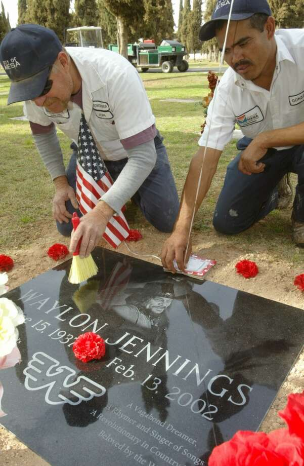 "Mesa Cemetery workers Jon Radu, left, and Gonzalo Meza spruce up Waylon Jennings new gravestone at the Mesa Cemetery in Mesa, Ariz., Tuesday, Feb. 18, 2003.  The flat black granite marker was installed Saturday, Feb. 15, 2003 two days after the first anniversary of the ""outlaw"" country singer-songwriter's death. Photo: RUSSELL GATES, AP"