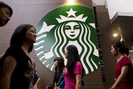 Pedestrians walk past a Starbucks Corp. store in the Luohu district of Shenzhen, China, on Monday, Aug. 4, 2014. Starbucks says it's taking measures to ensure food quality meets China and international standards in statement on an official microblog. Photographer: Brent Lewin/Bloomberg