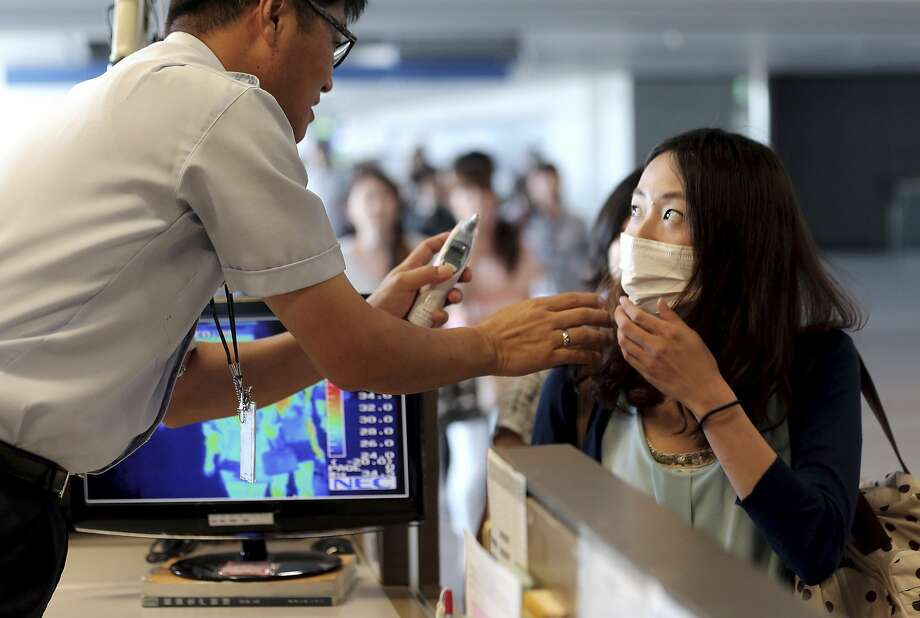 A South Korean quarantine officer, left, checks body temperature of a passenger against possible infections of Ebola virus at the Incheon International Airport in Incheon, South Korea, Friday, Aug. 8, 2014. South Korea has been stepping up monitoring of its citizens returning from trips to West Africa and other areas affected by the deadly Ebola virus. (AP Photo/Yonhap, Choe Jae-koo)  KOREA OUT Photo: Choe Jae-koo, Associated Press