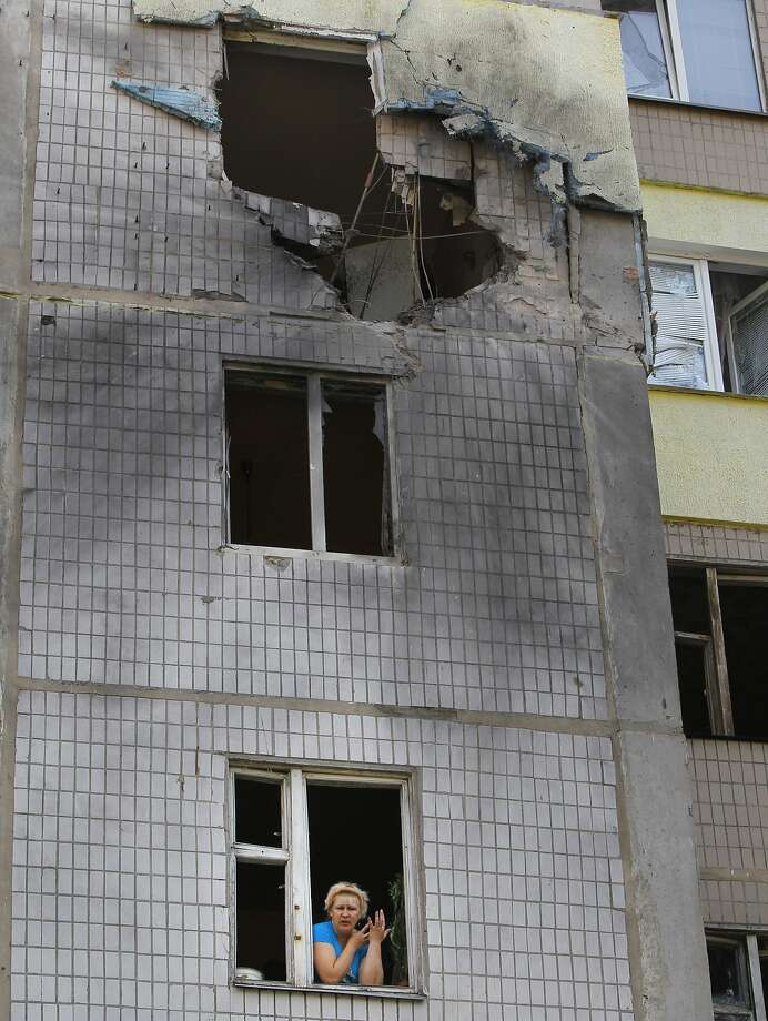 Marina Barsuk looks out the broken window of her apartment after shelling in Donetsk overnight. Photo: Sergei Grits, Associated Press