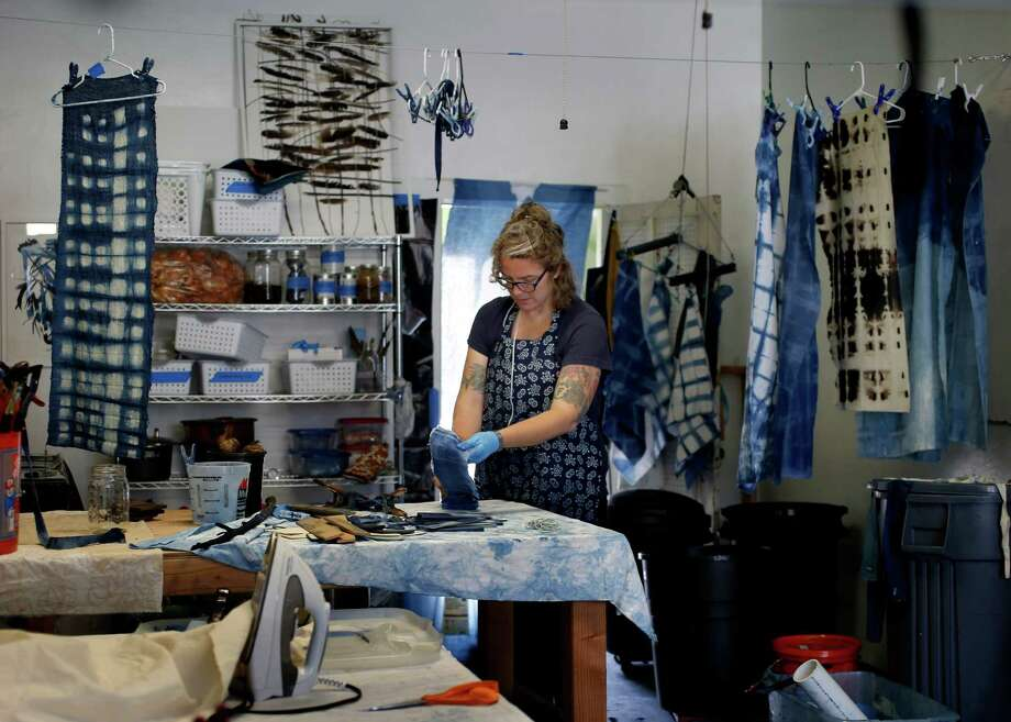 Carrie Crawford works on some recent shibori dyeing at her workshop Tuesday July 15, 2014. Carrie Crawford and her Mineral Workshop in Fairfax, Calif. produce shibori, a Japanese fabric dyeing technique she uses for wall hangings and pillows. Photo: Brant Ward, Staff Photographer / San Francisco Chronicle / ONLINE_YES
