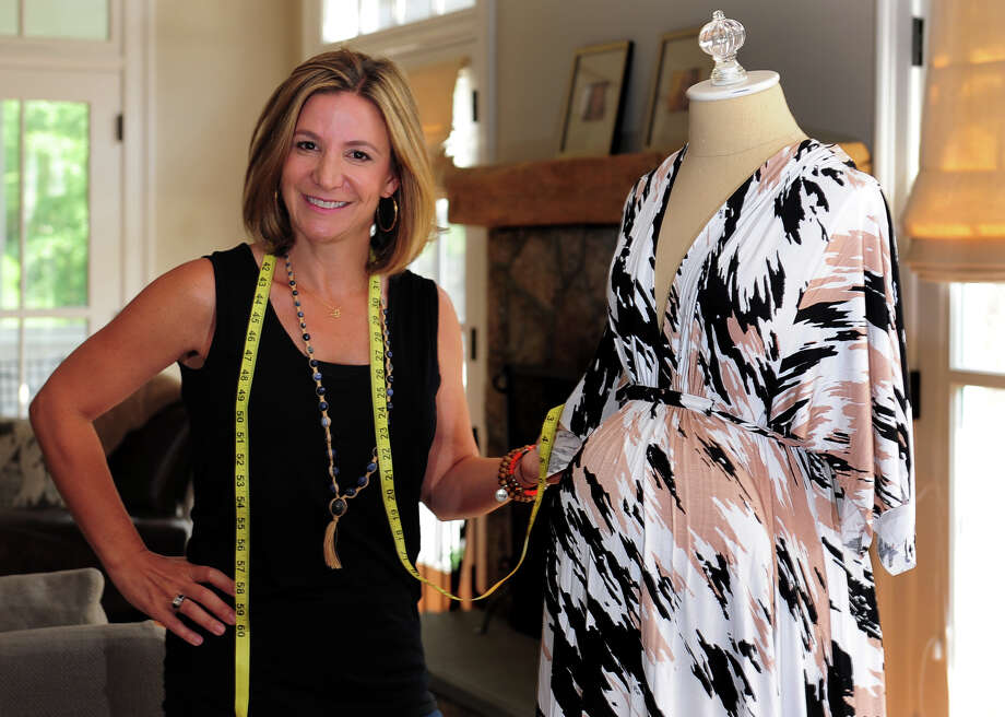 Jennifer Strom Simonte poses next to an example of maternity dress she markets through her business at her home in Westport on July 25. Photo: Christian Abraham / Connecticut Post