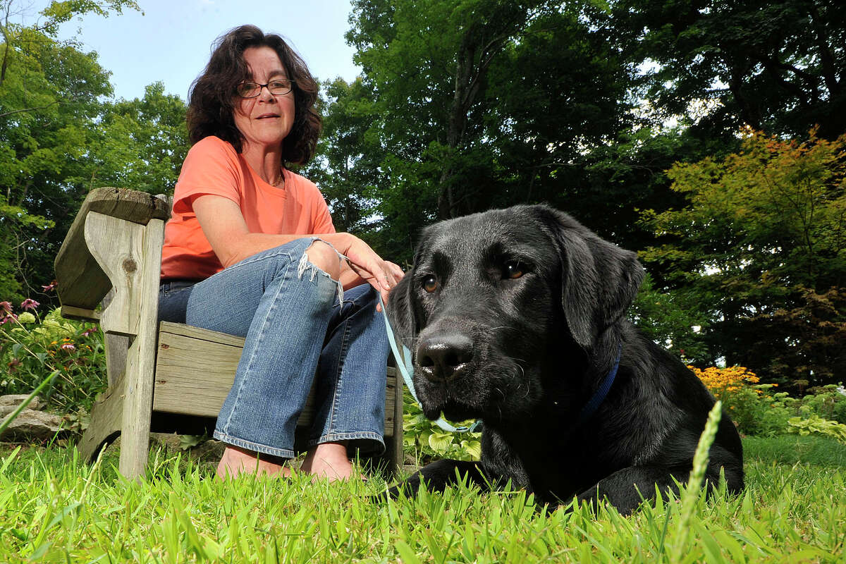 Catherine Simms poses with her dog, Blue, in her yard in North Stamford, Conn., on Thursday, Aug. 7, 2014. Simms started a petition to get a dog park in North Stamford.