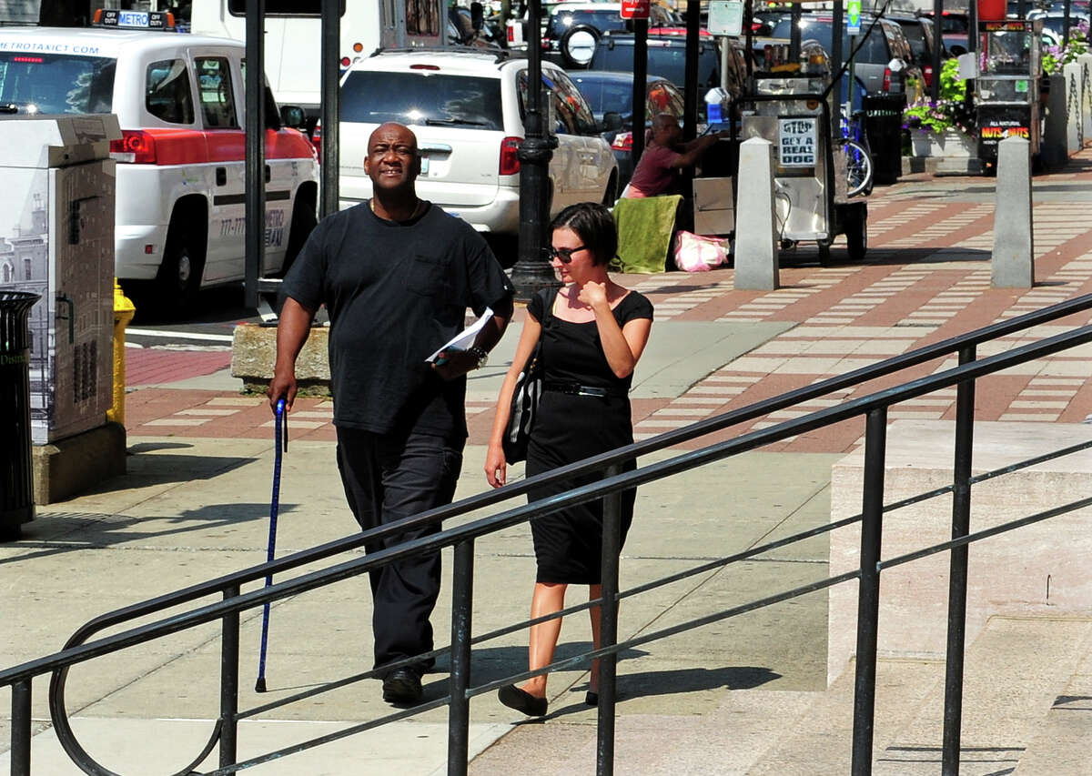 Bridgeport Police Officer Clive Higgins and his wife arrive at the Federal Courthouse in downtown New Haven, Conn. on Friday, Aug. 7, 2014. Higgins was indicted in his involvement in a police brutality incident at Beardsley Park in 2011.