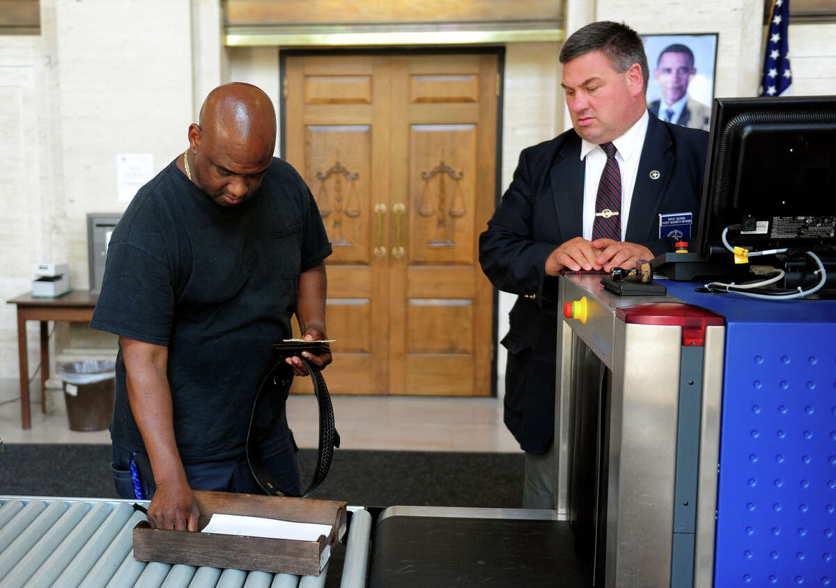 Bridgeport Police Officer Clive Higgins retrieves his belongings after going through the metal detector at the Federal Courthouse in downtown New Haven, Conn. on Friday, Aug. 7, 2014. Higgins was indicted in his involvement in a police brutality incident at Beardsley Park in 2011.