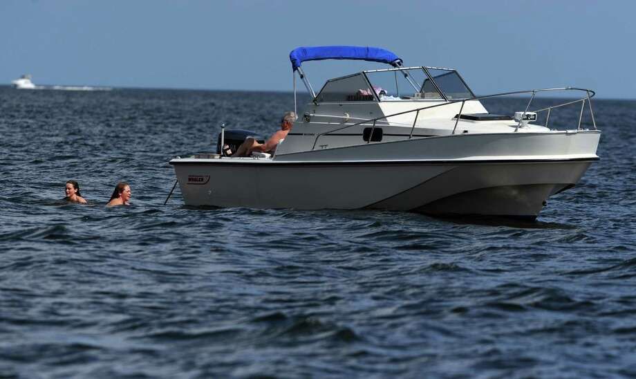 Beth and Doug McCaskey, of Fairfield, relax on their boat as daughters Isabelle, 19, and Mary Grace, 16, swim in the Long Island Sound off of Jennings Beach in Fairfield, Conn., Thursday, Aug. 7, 2014. Photo: Autumn Driscoll / Connecticut Post