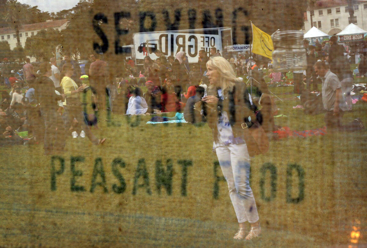A woman is seen reflected in a sign reading,