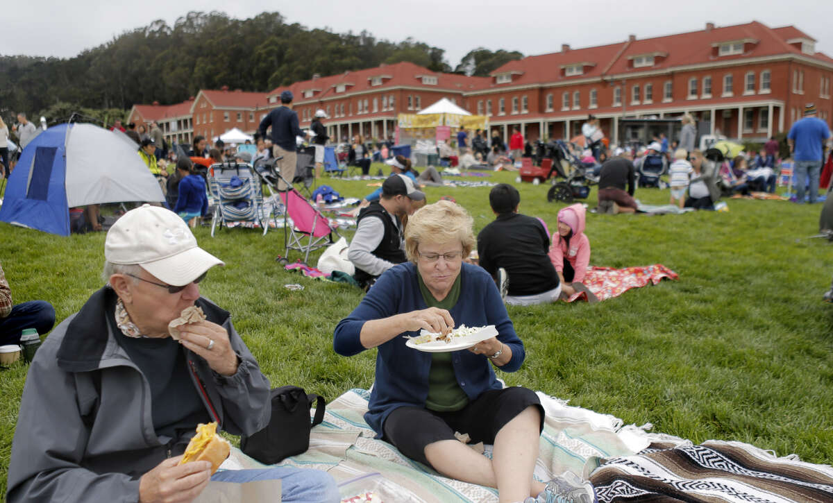 Ronnie and Cheryl Wester of Amarillo, Texas, enjoy food from Off the Grid's Sunday Picnic in the Presidio Main Post lawn in San Francisco, Calif., on Sunday, August 3, 2014. It is a gathering of food trucks with food stalls and even some produce markets that showcases the best of street food gatherings: the beer and wine, the crowds of all ages, the lawn, and lots and lots of food.