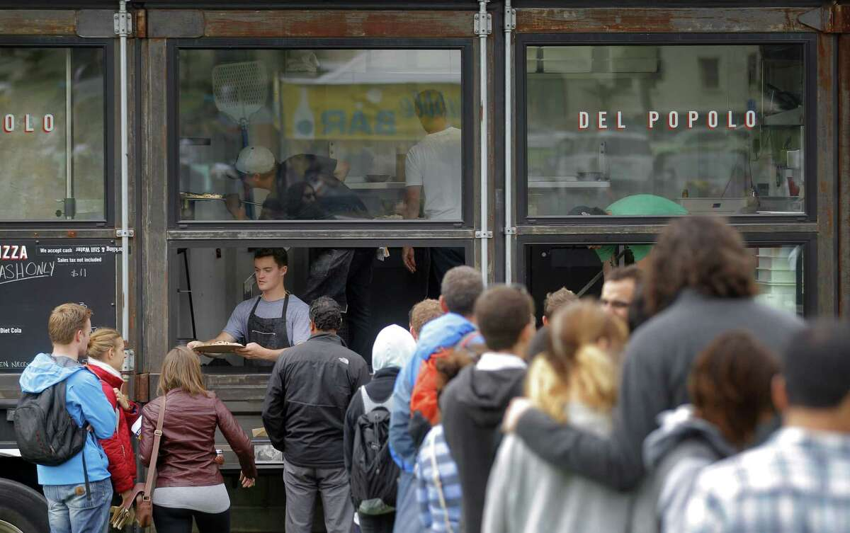 People line up at Del Popolo Pizza food truck during Off the Grid's Sunday Picnic in the Presidio Main Post lawn in San Francisco, Calif., on Sunday, August 3, 2014. It is a gathering of food trucks with food stalls and even some produce markets that showcases the best of street food gatherings: the beer and wine, the crowds of all ages, the lawn, and lots and lots of food.