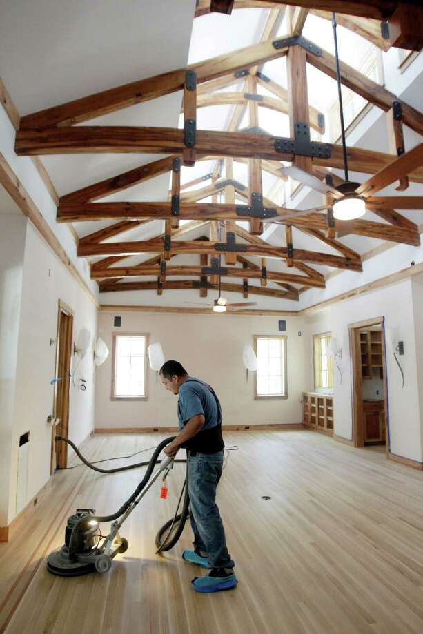 "Aurelio Miron, of Floor Designs of Houston, Inc., finishes the wooden floors. The rafters are made from trees from the house's site. The home was designed by local architect LaVerne Williams of Environment Associates, a pioneer of the ""green"" building movement. ( Mayra Beltran / Houston Chronicle ) Photo: Mayra Beltran, Staff / © 2014 Houston Chronicle"