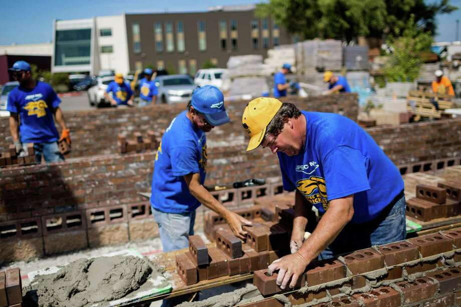 """Pitted against opposing teams, skilled masons and their assistants - known as """"tenders"""" - race against the clock to stack up organized walls of bricks at the fifth annual World Series of Bricklaying Friday, August 8, 2014, in Seattle, Wash. Craftsmen representing the state of Washington competed for cash and the opportunity to advance to the National Championship competition held next year in Las Vegas. Photo: JORDAN STEAD, SEATTLEPI.COM / SEATTLEPI.COM"""