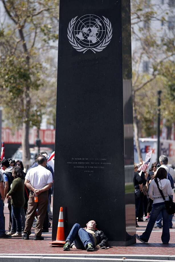 A man rests against the monument at United Nations Plaza. Photo: Michael Macor, The Chronicle