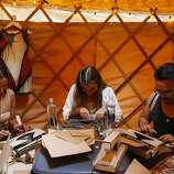 Maddie Porsnick, center, types a letter on a typewriter at the digital detox section of Outside Lands on Friday, Aug. 8, 2014 in San Francisco, Calif. Outside Lands is expected to draw in as many as 180,000 people this weekend.