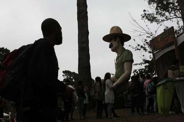 An Outside Land attendee passes Ranger Dave on his way into the music festival on Friday, Aug. 8, 2014 in San Francisco, Calif. Outside Lands is expected to dra