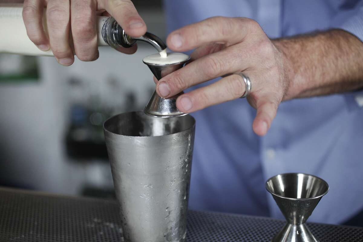 """Hard Water Bar Manager Erik Adkins measures out .5oz of Straus heavy cream to pour into a shaker cup as he prepares the """"Bourbon Lift"""", a drink featured on the menu at Hard Water August 5, 2014 at Hard Water in San Francisco, Calif."""