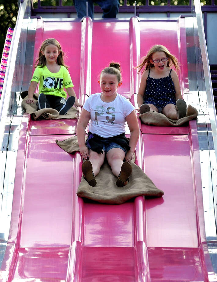 Makayla Dalessio, 7, left, Jordan Zealor, 9, and her sister Madison, 9, right, come down the slide, during Holy Rosary Parish Church's Festa! 2014 Italian Festival in Ansonia, Conn. on Friday, Aug. 7, 2014. The festival will also be open Saturday from 5 p.m. to 10 p.m. Photo: Christian Abraham / Connecticut Post