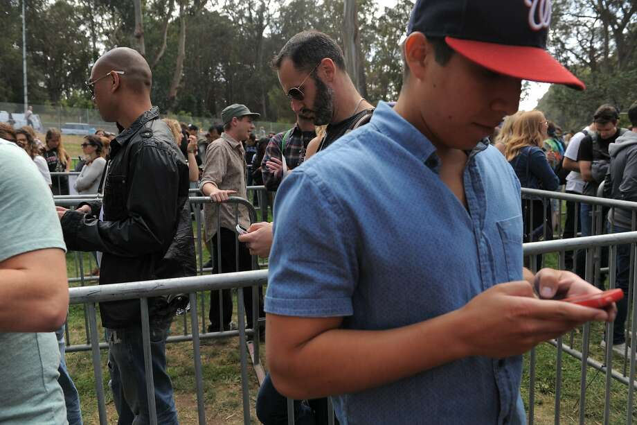 Festival goers check their phones as they wait in the will call line at Outside Lands Music Festival in Golden Gate Park on August 08, 2014 in San Francisco, CA. Photo: Craig Hudson, The Chronicle