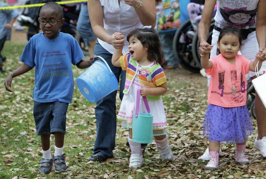 Darius Alex, 5, left, Isabel Barreda, 2, and Daria Galindo, 4, right, begin the Beeping Easter Egg Hunt at The Lighthouse of Houston Community Services Center, 3602 West Dallas, Saturday, March 23, 2013, in Houston.  Blind and visually impaired children took part in the annual Beeping Easter Egg Hunt that also included a hay ride by the Houston Farm and Ranch Club, games, face painting, and music. ( Melissa Phillip / Houston Chronicle ) Photo: Melissa Phillip, Staff / © 2013  Houston Chronicle