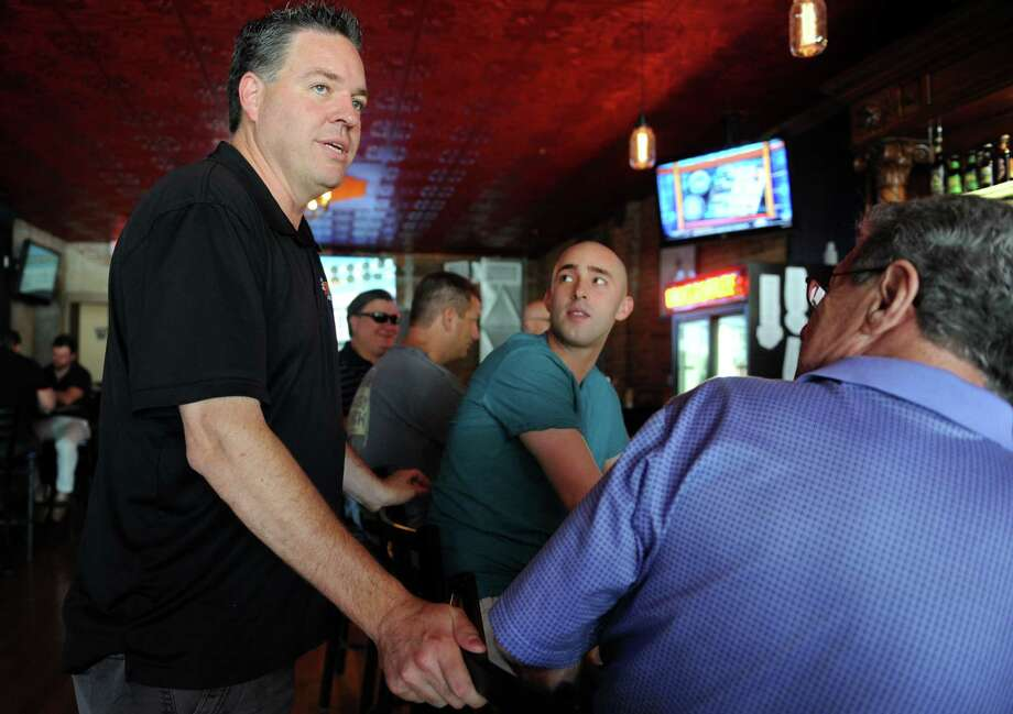 Part owner Chris Jones talks with customers Al Patuzzi, of Shelton, and his grandson Nick DeAngelo Wednesday Aug. 6, 2014, at Bricks and Barley Tavern in Shelton, Conn. Photo: Autumn Driscoll / Connecticut Post