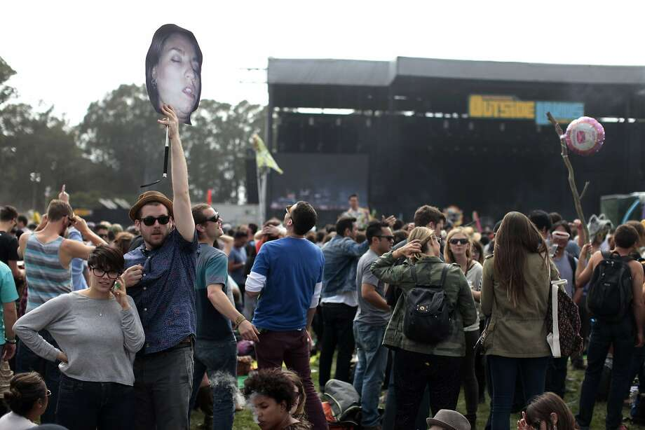 Justin Erwin holds a photo of his friend during Outside Lands at Golden Gate Park on Friday, Aug. 8, 2014 in San Francisco, Calif. Outside Lands is expected to draw in as many as 180,000 people this weekend. Photo: James Tensuan, The Chronicle