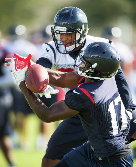 A.J. Bouye, left, breaks up a pass intended for Alec Lemon at camp. Bouye is competing to be the first Texans cornerback off the bench. Photo: Brett Coomer, Staff / © 2014 Houston Chronicle