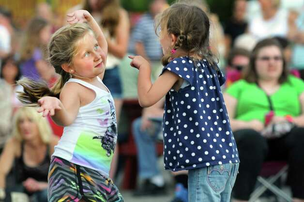 Jessica Beblowski, 6, of Rotterdam, left, dances with her cousin Samantha Cipriano, 5, to the music of Funk Evolution during Festa on Friday, Aug. 8, 2014, at Our Lady Queen of Peace church in Rotterdam, N.Y. The annual Festa, which features Italian food, raffles, a garage sale and carnival rides, continues Saturday from 5 to 11 p.m. and Sunday from 3 to 9 p.m. (Cindy Schultz / Times Union) Photo: Cindy Schultz / 10028093A