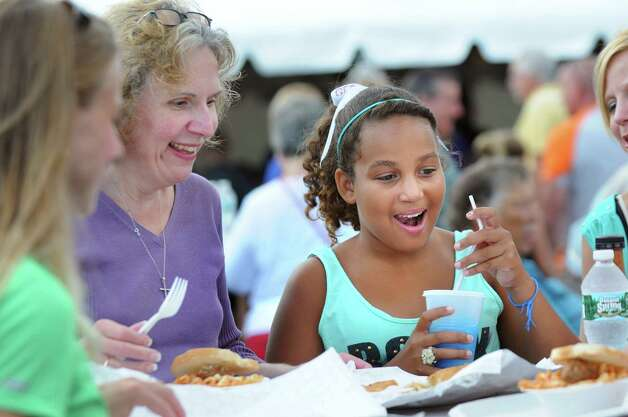 Zaria Walcott, 11, of Schenectady, center, has a slushy as she enjoys Italian treats with her godmother Brenda Jones during Festa on Friday, Aug. 8, 2014, at Our Lady Queen of Peace church in Rotterdam, N.Y. The annual Festa, which features Italian food, raffles, a garage sale and carnival rides, continues Saturday from 5 to 11 p.m. and Sunday from 3 to 9 p.m. (Cindy Schultz / Times Union) Photo: Cindy Schultz / 10028093A