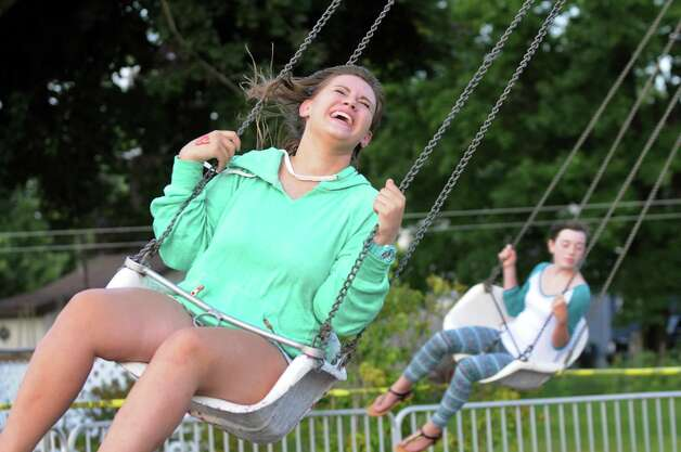 Shae Messemer, 14, of Rotterdam, left, takes a ride on the swings during Festa on Friday, Aug. 8, 2014, at Our Lady Queen of Peace Church in Rotterdam, N.Y. The annual Festa, which features Italian food, raffles, a garage sale and carnival rides, continues Saturday from 5 to 11 p.m. and Sunday from 3 to 9 p.m. (Cindy Schultz / Times Union) Photo: Cindy Schultz / 10028093A