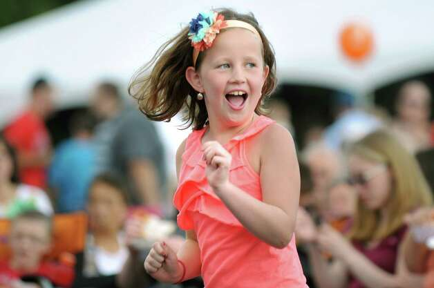 Katherine Cipriano, 7, of Saratoga Springs dances to the music of Funk Evolution during Festa on Friday, Aug. 8, 2014, at Our Lady Queen of Peace Church in Rotterdam, N.Y. The annual Festa, which features Italian food, raffles, a garage sale and carnival rides, continues Saturday from 5 to 11 p.m. and Sunday from 3 to 9 p.m. (Cindy Schultz / Times Union) Photo: Cindy Schultz / 10028093A