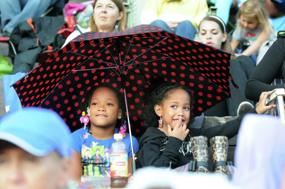 "Jalani Aponte, 7, of Troy, left, and her sister Jayla Aponte, 5, remain under an umbrella when the skies clear for the Park Playhouse outdoor production of ""Oliver"" on Thursday, Aug. 7, 2014, at Washington Park in Albany, N.Y. (Cindy Schultz / Times Union) Photo: Cindy Schultz / 00028077A"