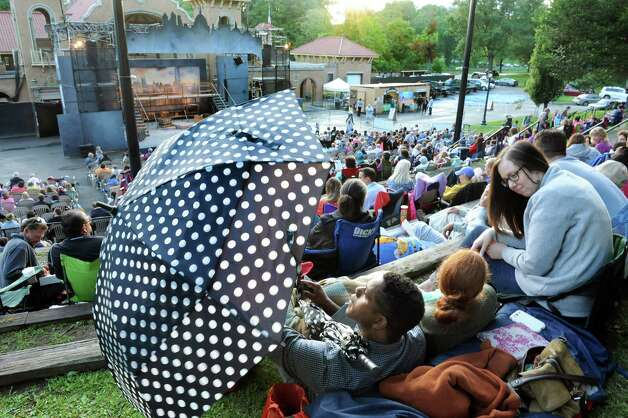 "Cornelius Powell of Troy, left, takes down an umbrella when the skies clear for the Park Playhouse outdoor production of ""Oliver"" on Thursday, Aug. 7, 2014, at Washington Park in Albany, N.Y. Joining him are his wife, Sarah Powell, center, and their friend Ashli Allen. (Cindy Schultz / Times Union) Photo: Cindy Schultz / 00028077A"