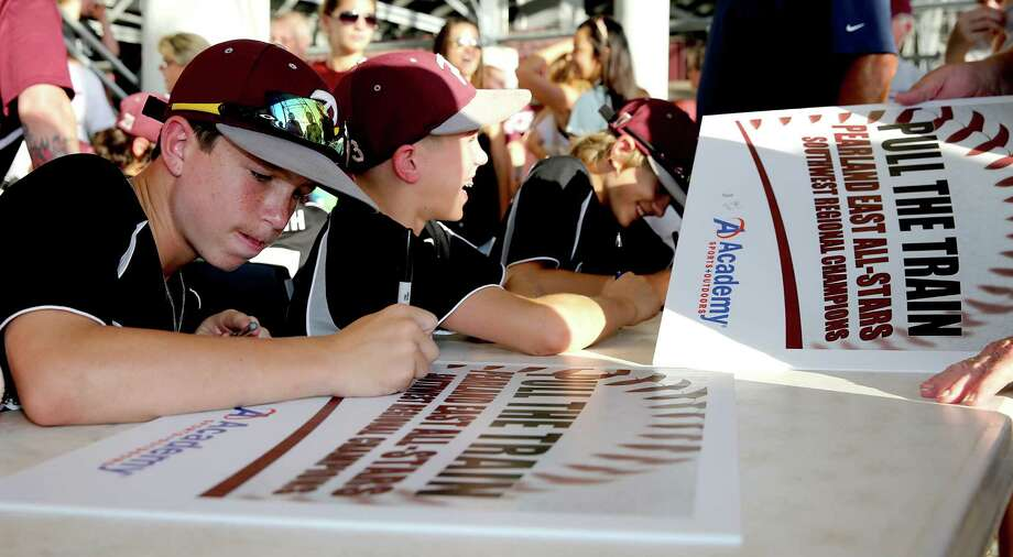 Cole Smajstrla, left, and other members of the Pearland Little League East team sign autographs at a fundraiser at Pearland's Rig football stadium Friday. They leave for Williamsport, Pa., early Saturday. Photo: Thomas B. Shea / © 2014 Thomas B. Shea