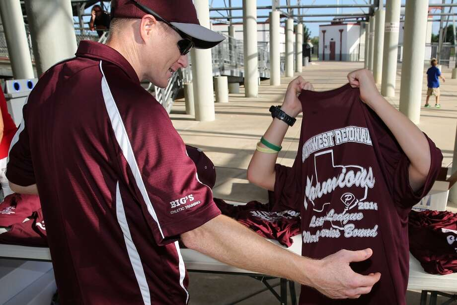 8/8/14: Kyle Moses helps his son Luke Moses try on a Southwest Regional Champion t-shirt at the Pearland Little League send off fundraise party at the RIG in Pearland, TX. (Photo by Thomas B. Shea for the Houston Chronicle).