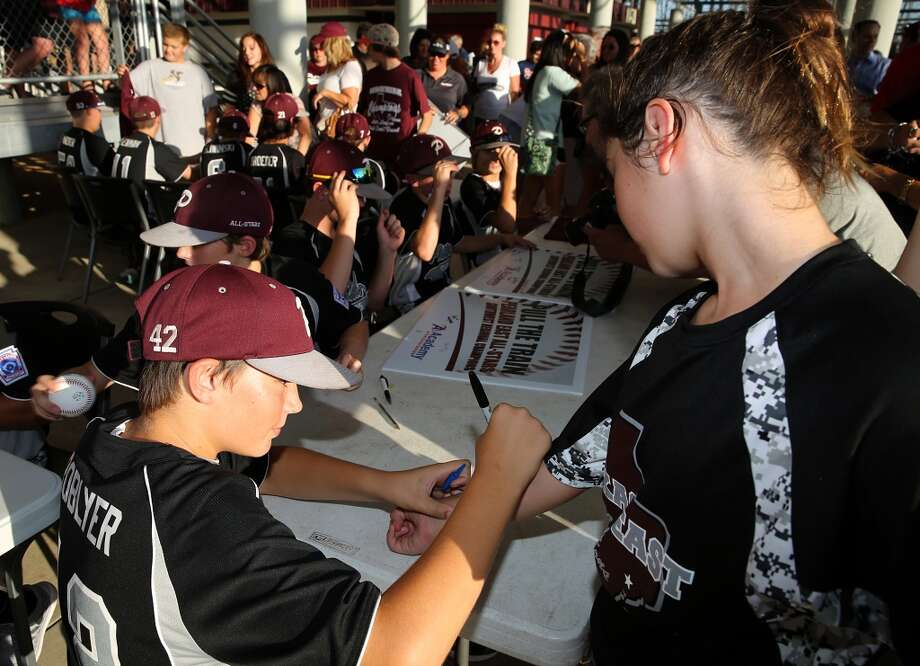 8/8/14: Layne Roblyer, #42 sign Isabella Terranova, age 12 arm at the Pearland Little League send off fundraise party at the RIG in Pearland, TX. Isabella's brother is Christian Terranova who is on the team. (Photo by Thomas B. Shea for the Houston Chronicle).