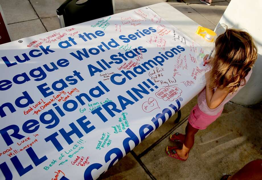 8/8/14:A little girls signs a good luck banner at the Pearland Little League send off fundraise party at the RIG in Pearland, TX. (Photo by Thomas B. Shea for the Houston Chronicle).