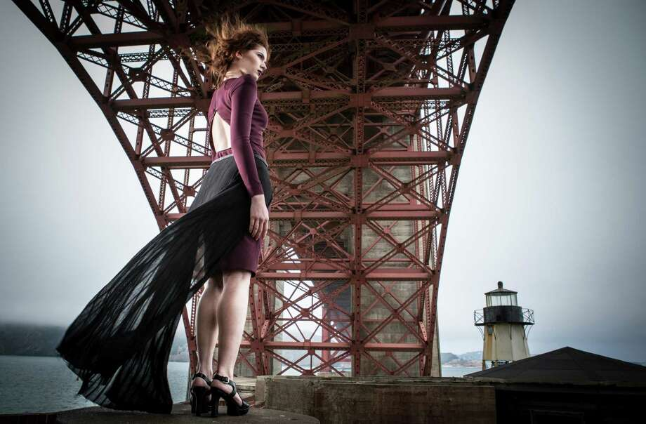 """To the lighthouse: Scaffolding of the Golden Gate Bridge towers overhead as Emily stands her ground at Fort Point in a Tom Ford oxblood open-back zipper dress, $8,600, Neiman Marcus; black """"Entangle"""" skirt, Melissa Fleis, $575, www.melissafleis.com; Lauren by Ralph Lauren heels, $119, Macy's Union Square. Photo: Russell Yip / Russell Yip / The Chronicle / ONLINE_YES"""
