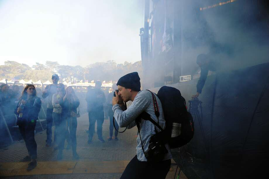 A photographer snaps photos amidst the smoke during the performance of Disclosure on the Lands End stage at Outside Lands Music Festival in Golden Gate Park on August 08, 2014 in San Francisco, CA. Photo: Craig Hudson, The Chronicle