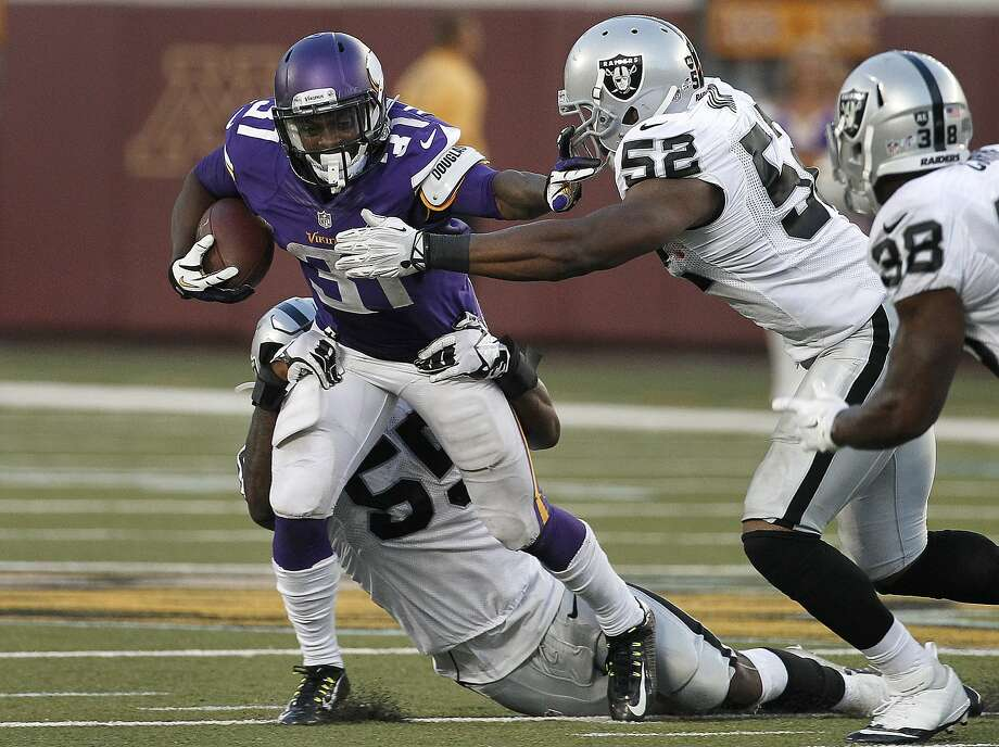 Linebackers Sio Moore (55) and Khalil Mack (52) try to bring down Vikings running back Jerick McKinnon in the first half. Photo: Ann Heisenfelt, Associated Press